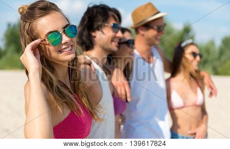True friendship. Pleasant charming young woman embracing with her friends and expressing joy while resting on the background together