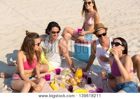 Nice refreshment. Pleasant cheerful friends sitting on the sand and having a picnic while resting on the beach