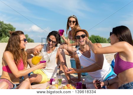 Bright summer. Cheerful smiling friends sitting on the blanket and resting on the beach while having a picnic