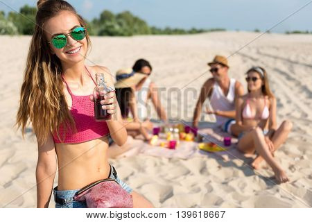 YOLO. Cheerful smiling beautiful woman drinking lemonade while her friends sitting in the background and having picnic on the beach