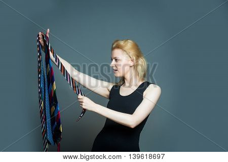 Young fashionable woman with pretty serious face and stylish blonde hair holding many different colorful ties in hand posing on gray studio background