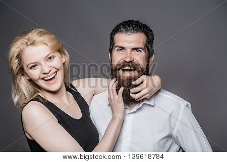 young couple of woman with pretty smiling face and blonde hair in black vest and handsome bearded man with long beard in white shirt in studio on grey background