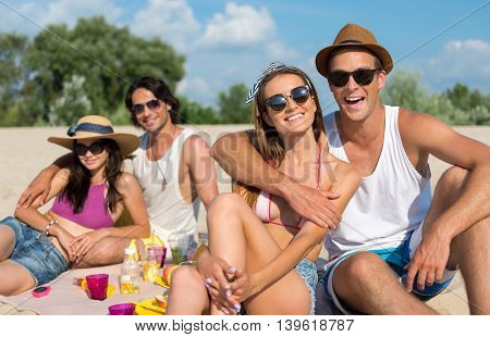 Enjoy the moment. Cheerful delighted smiling friends sitting on the blanket and having a picnic while resting on the beach together