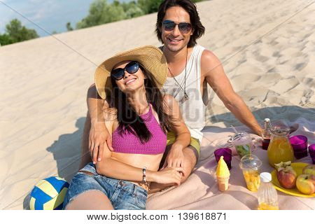 Happy together. Positive content couple smiling and lying on the sand while having a picnic on the beach