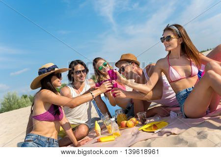 Emotionally charged. Delighted overjoyed smiling friends sitting on the blanket and drinking while having picnic on the beach