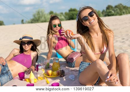 Joyful atmosphere. Cheerful beautiful friends sitting on the beach and having a picnic while relaxing on the beach