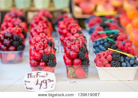 Berries fruits at a marketplace. Blueberries, raspberries, strawberries, cherries and blackberries on the market.