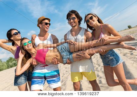 Break through the routine. Cheerful delighted friends holding young beautiful woman while having rest on the beach