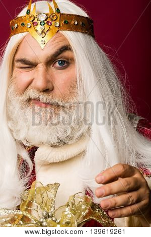 old bearded zeus man wizard in jewellery golden crown with blue lenses in eyes with long gray beard and white hair has winking face on purple background
