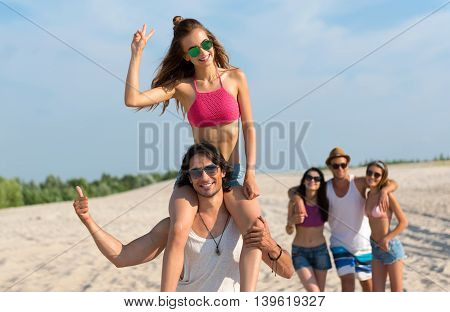 Best summer. Overjoyed smiling handsome, man holding his girlfriend on the shoulders while their friends resting on the beach in the background