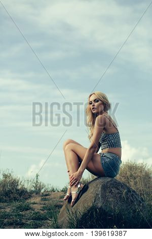 Pretty Woman On Stone And Blue Sky