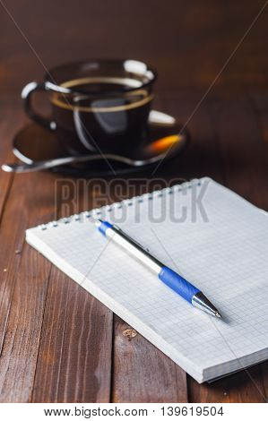 Notebook With Pen Lie Wooden Table, And Next To A Cup Of Coffee.