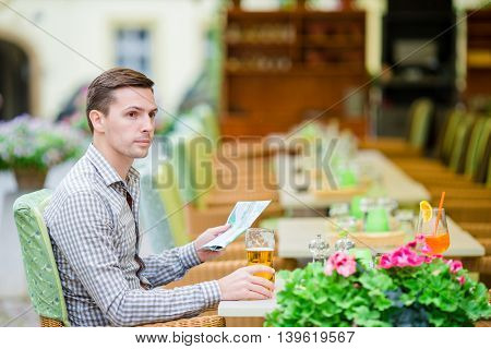 Caucasian young european man in a blue shirt in outdoors cafe.
