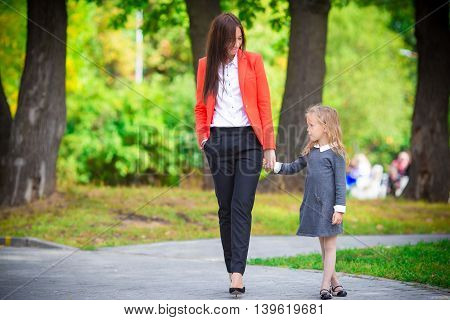 Mother brings her little daughter to school.
