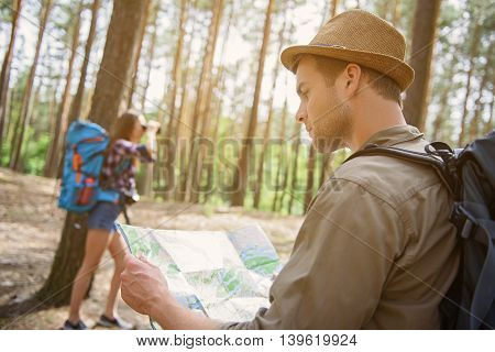 Pretty couple is making touristic travel in forest. Man is standing and looking at map with seriousness. Woman is looking into binoculars with interest