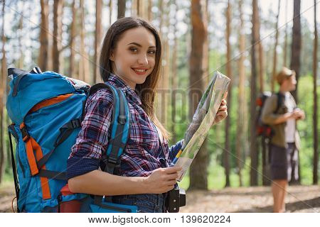 Cheerful tourists are traveling in forest. Woman is holding a map and smiling. She is looking at camera with happiness. Man is standing on background
