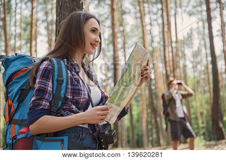 Joyful tourists are enjoying nature with happiness. They are standing and smiling. Woman is holding a map. Man is using binoculars on background