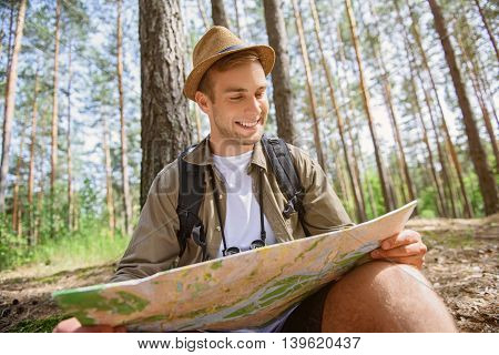 Joyful young man is reading a map and smiling. He is sitting in forest with touristic equipment