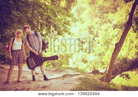 Adventure tourism enjoying summer time together - Hiking young couple with guitar backpack tramping on forest road sunny countryside
