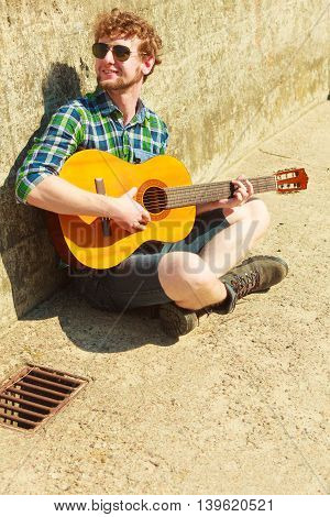 Music and people concept. Young bearded hipster man with guitar outdoor on street