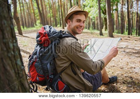 I chose my route. Joyful young tourist is holding a map and looking at camera with happiness. Man is sitting and smiling