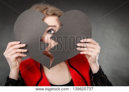 Depression and sadness concept. Young person with broken heart full of negative sad emotions. Woman covering his face by two parts of black love symbol.