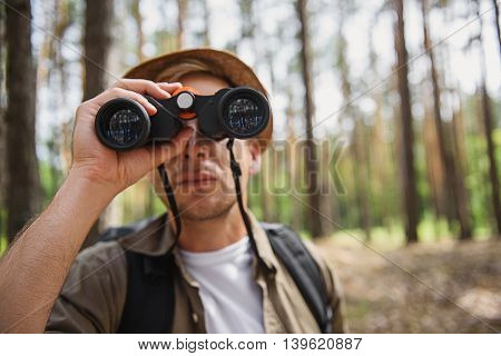 Young tourist is lost in forest. He is standing and looking into the binoculars with seriousness