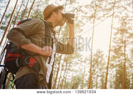 Low angle of young man is looking into binoculars with interest. He is standing in forest and carrying backpack