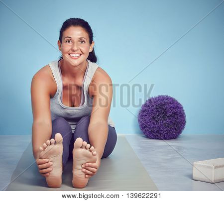 Smiling Young Yoga Woman Stretching On Her Mat