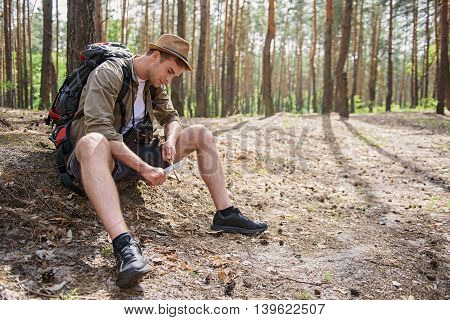 Skillful young man is using a knife to whittle a stick out with concentration. He is sitting on ground in forest