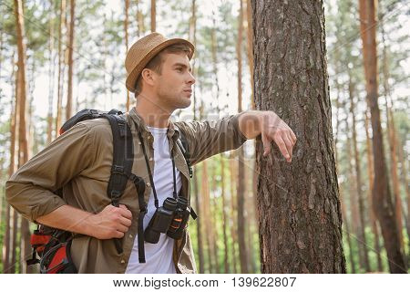 Young tourist is resting during journey. He is standing and leaning arm on tree. Man is standing and looking forward with aspiration
