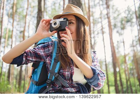 Cheerful young woman is taking photos of forest. She is sitting and smiling
