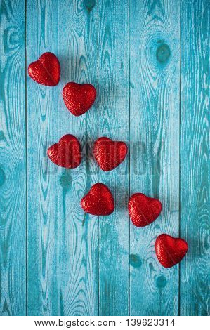 many red hearts on a blue background with wood texture