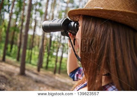 Happy female tourist is enjoying nature in forest. She is standing and looking into binoculars. Woman is smiling
