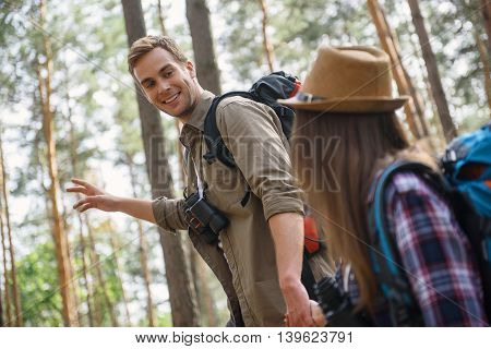 Come with me and see that beauty of nature. Joyful young man is holding female hand and smiling. He is standing and pointing arm sideways