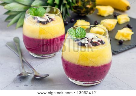 Two layer smoothie with black currant quick oats yogurt and pineapple banana horizontal