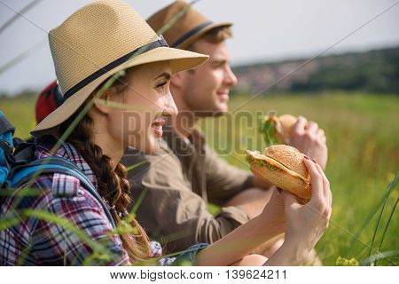 Happy couple making break after hiking. They are eating food and smiling. Man and woman are sitting on grass in meadow
