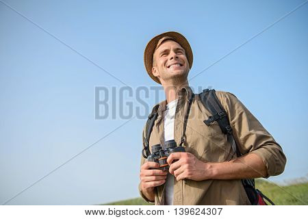 Joyful male tourist is hiking on meadow. He is standing and smiling. Man is holding binoculars