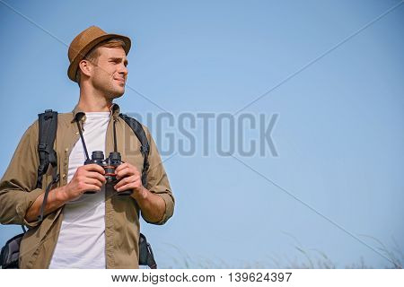 Young tourist is searching for location on field. He is standing and holding binoculars. Man is looking aside with anticipation