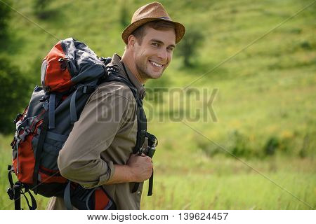 Joyful young man is making touristic journey. He is standing on meadow and smiling. Traveler is looking at camera with happiness