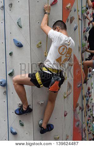 An asian man climbing indoor vertical wall