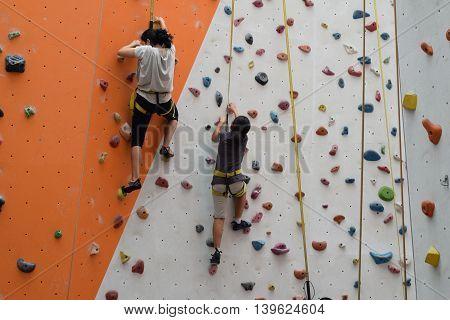 Two asian women climbing indoor vertical wall