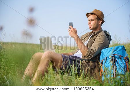 Cheerful young man is resting on meadow. He is sitting on chair and using mobile phone with interest. Tourist is holding laptop on knees