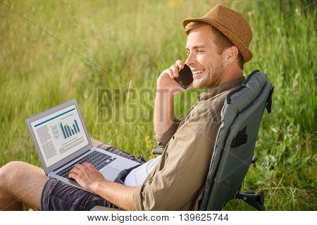 Happy young guy is talking on mobile phone and smiling. He is sitting on chair in nature. Tourist is holding laptop