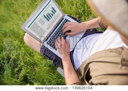 Top view of young man typing on laptop with inspiration. He is sitting on chair on grass