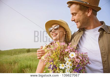 Happy loving couple enjoying the nature on field. They are laughing. Man is standing and embracing woman with flowers