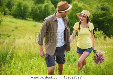 Carefree man and woman are dating in nature. They are walking on meadow and holding hands. Lovers are looking at each other and smiling