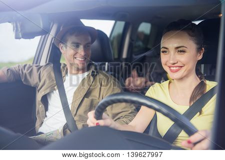 Joyful man and woman are enjoying trip on car. They are sitting and laughing