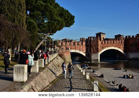 VERONA, ITALY - FEBRUARY 5: Tourists visit medieval Scaliger Bridge and Adige River banks FEBRUARY 5, 2016 in Verona, Italy