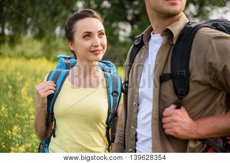 Happy young tourists are enjoying nature together. Woman is standing and looking at man with love. She is smiling
